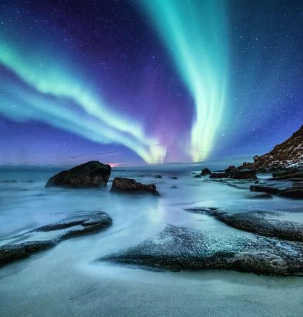 Zorza polarna na Lofotach w Norwegii. Zielona zorza polarna nad brzegiem oceanu. Nocne niebo z polarnymi światłami. Nocny zimowy krajobraz z zorzą polarną i odbiciem na powierzchni wody. Naturalne tło w Norwegii
