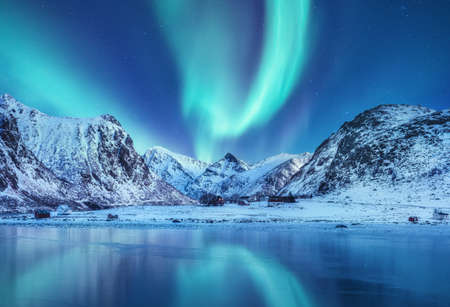 Aurora borealis on the Lofoten islands, Norway. Green northern lights above mountains. Night sky with polar lights. Night winter landscape with aurora and reflection on the water surface. Norway-image Stockfoto