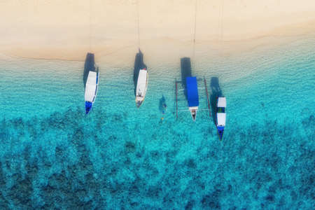 Boats on the water surface from top view. Turquoise water background from top view. Summer seascape from air. Gili Meno island, Indonesia. Travel - image