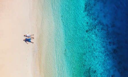 Aerial view of a people couple on the beach on Bali, Indonesia. Vacation and adventure. Beach and turquoise water. Top view from drone at beach, azure sea and relax couple. Travel and relax - image Imagens