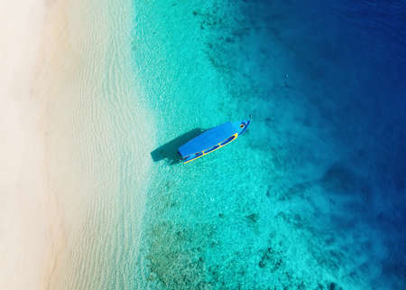 Boat on the water surface from top view. Turquoise water background from top view. Summer seascape from air. Gili Meno island, Indonesia. Travel - image