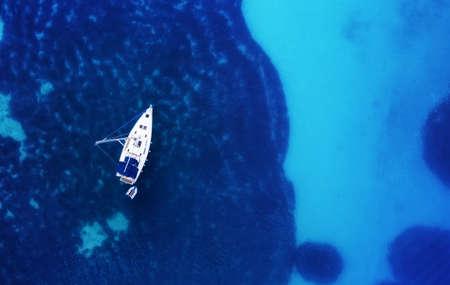 Yacht auf der Wasseroberfläche aus der Draufsicht. Türkisfarbener Wasserhintergrund aus der Draufsicht. Sommermeerblick aus der Luft. Kroatien. Reisen - Bild