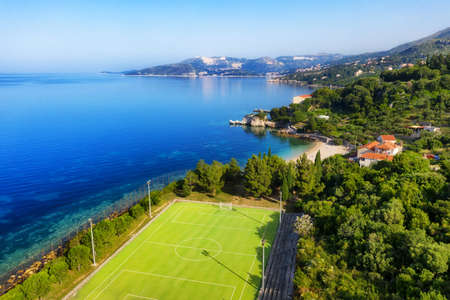 Aerial view on the football field near sea coast. Sport background.