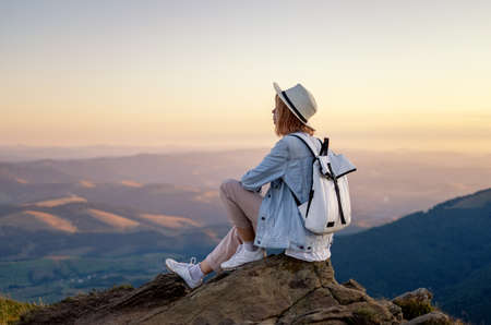Hiker with a backpack in the mountains. Young girl resting in the mountains during sunset. Mountains and people. Adventure and travel - image