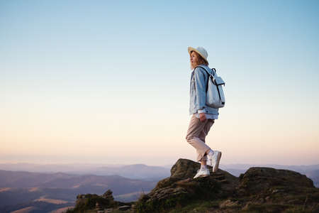 Hiker with a backpack in the mountains. Young girl walking in the mountains during sunset. Mountains and people. Adventure and travel - image Banco de Imagens