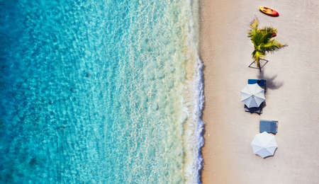 Umbrellas, Beach and ocean as a background from top view. Azure water background from top view. Summer seascape from air. Travel - image Banco de Imagens