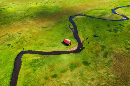 Iceland. Aerial view on the alone house, field and river. Landscape in the Iceland at the day time. Landscape from drone. Travel - image Banco de Imagens