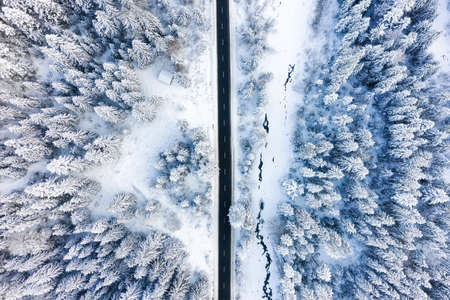 Aerial view on the road and forest at the winter time. Natural winter landscape from air. Forest under snow at the winter time. Winter travel - image