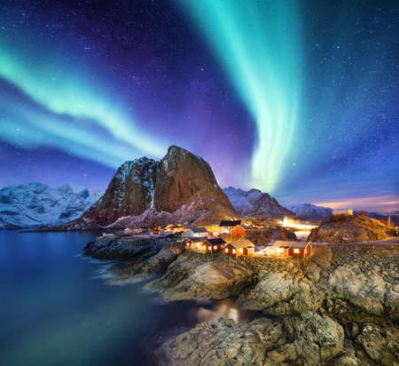 Aurora Borealis above Reine, Lofoten islands, Norway. Nothen light, mountains and houses. Winter landscape at the night time. Norway travel - image 免版税图像