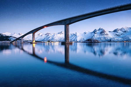 Bridge, water and night sky with stars. Reflection on the water surface. Natural landscape in the Norway at the night time. Travel  - image
