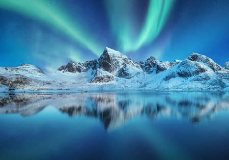 Aurora Borealis, Lofoten islands, Norway. Northen lights, mountains and reflection on the water. Winter landscape during polar lights. Norway travel - image Banco de Imagens
