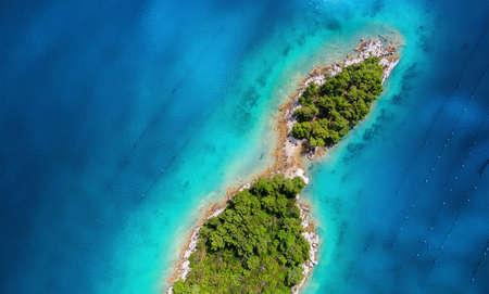 Vista aérea de islas en el mar. Paisaje marino desde el aire en el horario de verano. Agua azul e islas con bosque. Viajes - imagen