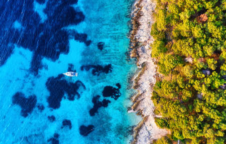 Blue water background and coast with forest from top view. Yacht on the water surface from top view. Summer seascape from air. Croatia. Travel - image