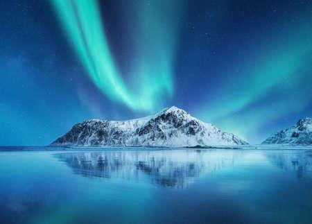 Aurora Borealis, islas Lofoten, Noruega. Luces del norte, montañas y reflejo en el agua. Paisaje invernal durante las luces polares. Noruega viajes - imagen