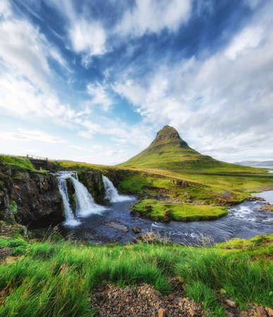 Kirkjufell. Mountains and waterfall in the Iceland. Natural landscape in the summer. Grass and river. Famous place. Iceland travel - image