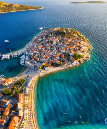 Primosten town, Croatia. View of the city from the air. Seascape with beach and old town. View from drone on the peninsula with houses. Landscape during sunset. Travel image Stock Photo