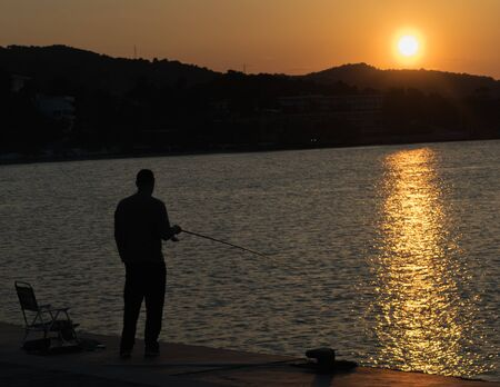 chilling out: Fisherman chilling out against the beautiful sunset in Greece.