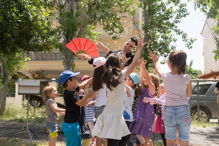 magic show: Date: 1752015. Location: Park in Athens. Magic show with Tristan. Happy kids trying to catch confetti.