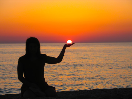 amazing stunning: Beautiful sunset with a girls silhouette holding the sun. Stock Photo