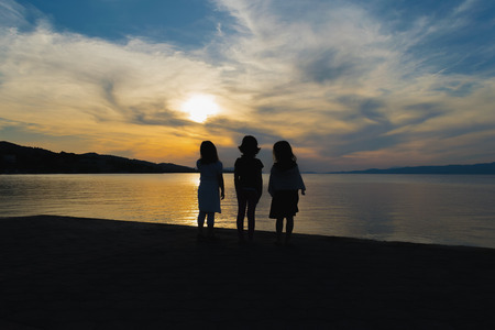 dramatic sky: Three little girls watching the sunset against a dramatic sky.
