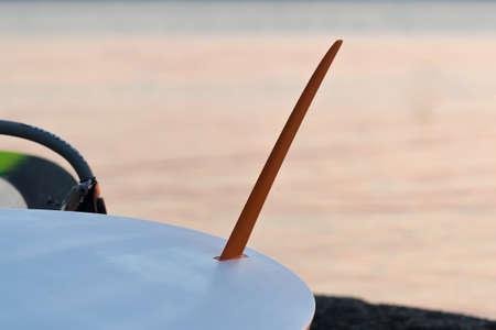 surfboard fin: Surfboard fin against the ocean. Stock Photo