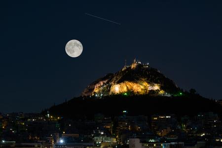 noche y luna: Montaña Lycabettus en Atenas Grecia contra la luna llena de agosto y una estrella fugaz. Foto de archivo