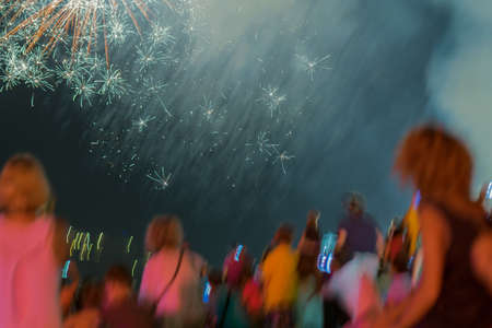 festival moments: Fireworks at night against the blurred audience. A beautiful moment of wonderment. Stock Photo
