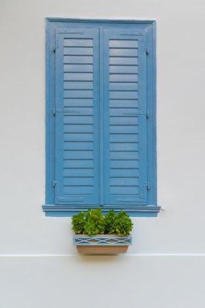 greek pot: Traditional old wooden blue window with a pot of flowers at the front in Nafplio Greece.