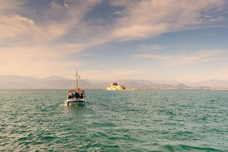 Boat with local people and tourists going to Bourtzi castle for a tour at Nafplio in Greece.