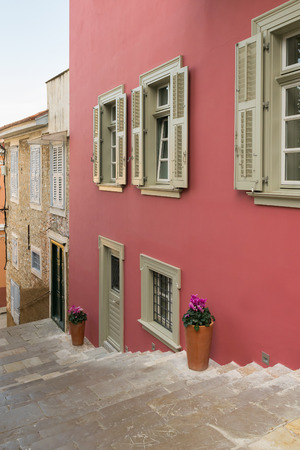 nafplio: Traditional alley at Nafplio in Greece with pink walls and flowers.