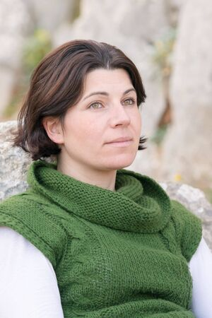 mid thirties: Portrait of a beautiful woman in her mid thirties with green eyes wearing a green sweater. Stock Photo