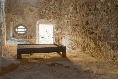 nafplio: Nafplio, Greece, 28 December 2015. Old prison cell at Palamidi castle in Greece with a wooden bed.