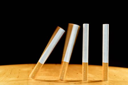 brings: Cigarettes domino falling as a concept of the addiction that cigarettes create. One cigarette brings another and the addiction continues. Stock Photo