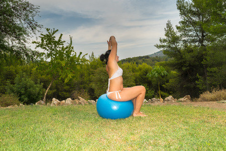 ball stretching: Woman sitting on a fitness ball stretching out her body.