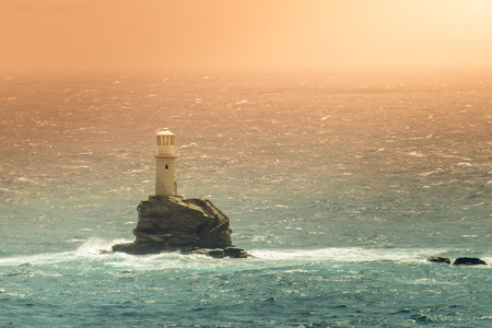 Tourlitis lighthouse in Andros island in Greece. Golden hour. Imagens