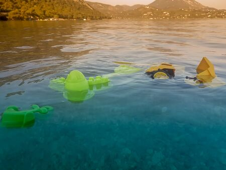Kid toys floating in the sea. Concept of sadness after someone drowned. Banco de Imagens