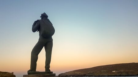 Andros, Greece 23 August 2018. The back of the unknown sailor in Andros island in Greece waving to the sea against the sunset. 에디토리얼