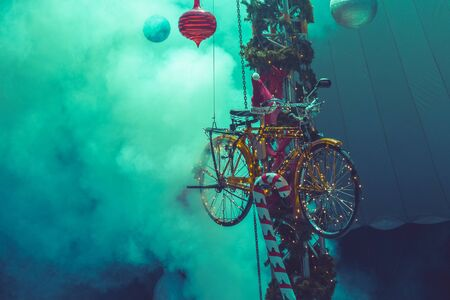 Christmas bicycle decoration with smoke as background. Close up look with greenish colors.