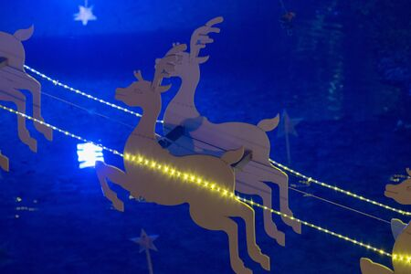 Flying deer christmas decoration with against blue lights. Stok Fotoğraf