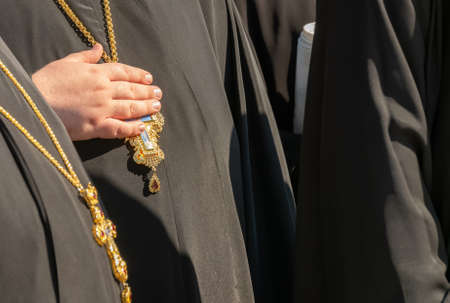 Orthodox priest holding cross hanging from neck.
