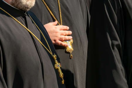 Priest holding the cross hanging from his neck. 스톡 콘텐츠