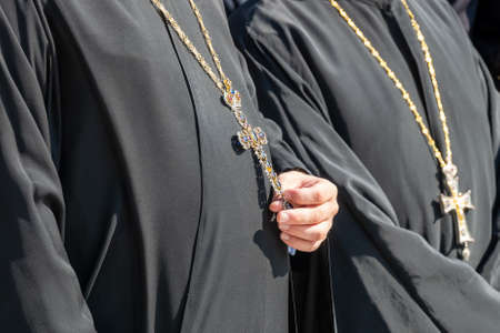 Close up of a priest holding the cross hanging from his neck.