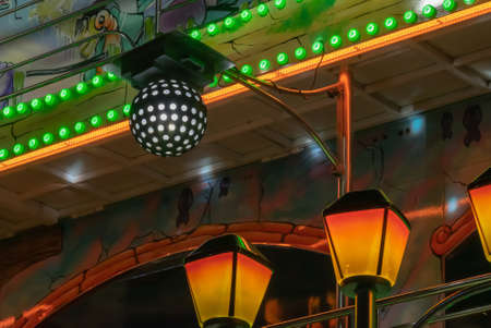 Retro disco ball and lights at a funfair.
