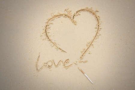 romanticism: Heart drawn on sand. Horizontal composition. Stock Photo
