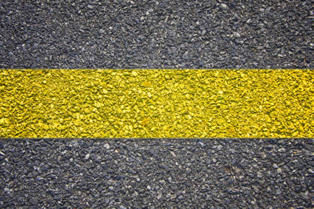 grungy, dirty view of asphalt with distinct yellow stripe  black texture  photo
