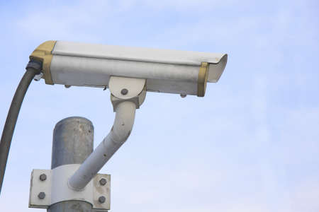 Surveillance Security Camera or CCTV on blue sky photo