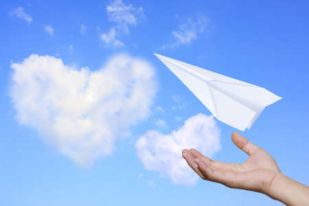Aircraft paper hand blue sky with clouds, heart of love Stock Photo - 13526899