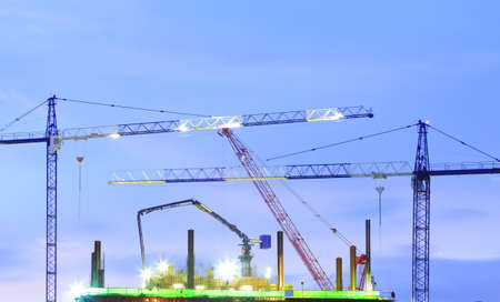 couple of cranes on a construction site with a blue evening sky backdrop Stock Photo - 15245624