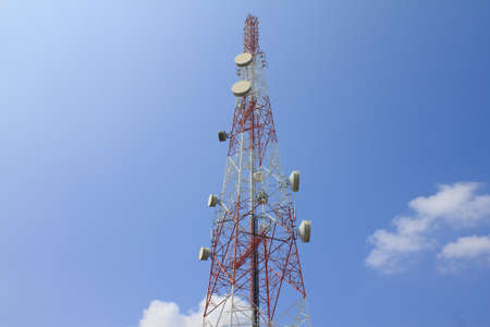telco: Red and white tower of communications with with a lot of different antennas under clear sky.