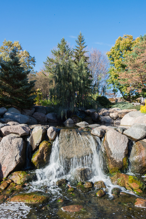 water feature: This is a small waterfall as part of a water feature with boulders. This is in the Minnesota Landscape Arboretum. Stock Photo
